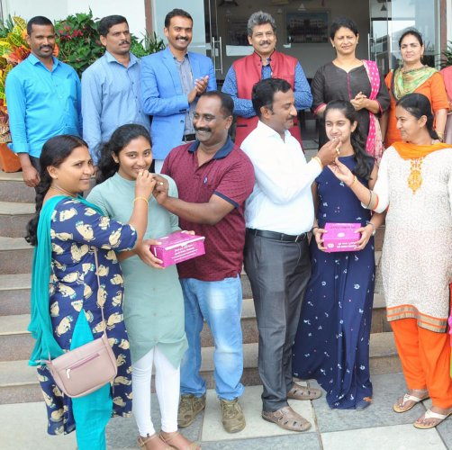 Bhumika Naidu C R and Yukta G Swamy, the district toppers in SSLC exams celebrate at St Mary's School, Chikkamagaluru, with their parents on Tuesday.