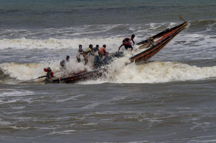 Fishermen try to control their boat amidst rough sea waters at Puri beach. PTI photo