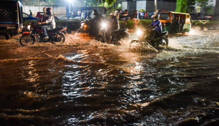 Cubbon Park near the metro station was flooded following the downpour on Tuesday. (Right, below) Two women stranded near Chinnaswamy Stadium. DH PHOTOS/B K JANARDHAN