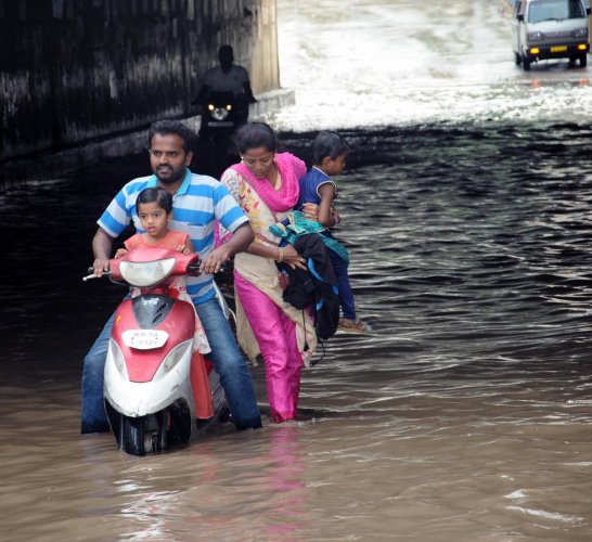 A couple had a tough time in crossing the flooded railway underbridge in Satyanarayanapet, Ballari, on Wednesday.