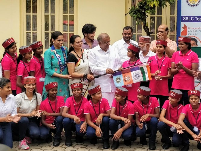 Minister G T Devegowda hands over the flags to the tribal girls in Mysuru, recently. Secretary of Tiger Adventure Foundation Suma Mahesh and chairman D S D Solanki are seen.