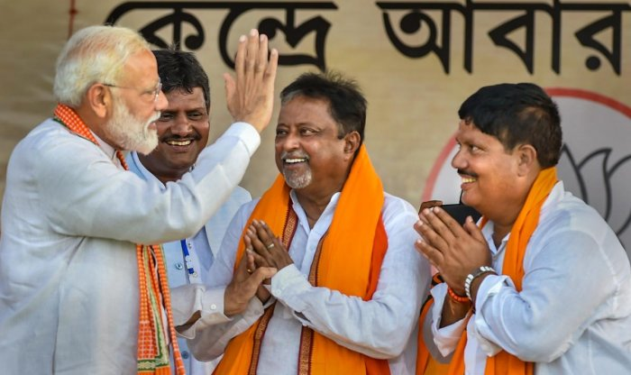 Prime Minister Narendra Modi being greeted by BJP leader Mukul Roy and party candidate from Barrackpore constituency Arjun Singh (R) during an election campaign rally for ongoing Lok Sabha polls, at Jilebi in North 24 Parganas district of West Bengal on April 29, 2019. (PTI Photo)