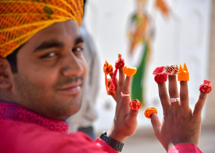 Artist Pawan Vyas, poses with miniatures of Rajasthani turbans, in Bikaner on March 29. PTI
