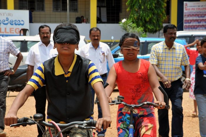 Students ride bicycles blindfolded in Chikkamagaluru on Thursday. DH photo