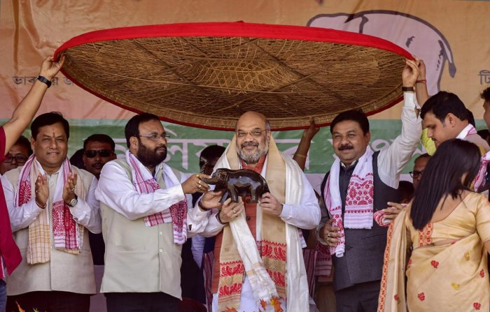 Bharatiya Janata Party National President Amit Shah being felicitated by his party leaders during an election rally ahead of the Lok Sabha polls, in Nagaon District. PTI photo