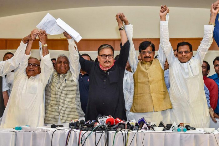 Rashtriya Janata Dal MP Manoj Jha, state's party President Ramchandra Purbey and Congress' state president Madan Mohan Jha join hands after announcing the grand alliance's candidates list for upcoming Lok Sabha election 2019, in Patna on March 22, 2019. (PTI Photo)