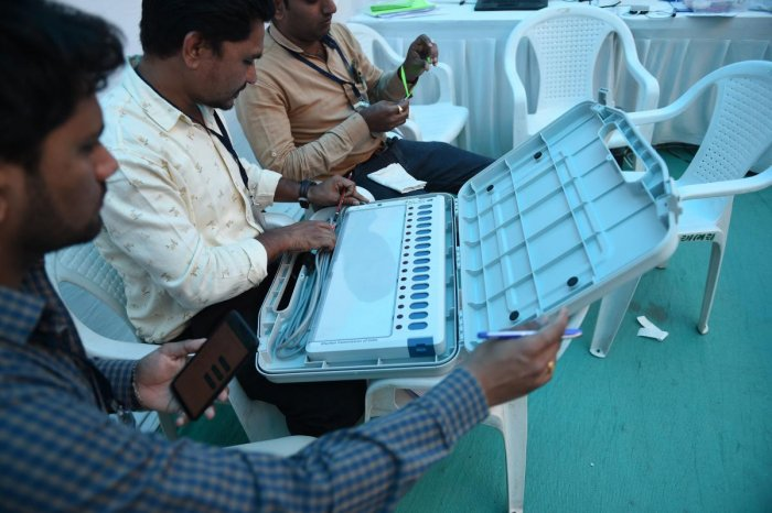 Election officials check an Electronic Voting Machine (EVM) at a distribution centre ahead of the Lok Sabha elections in Ahmedabad. AFP