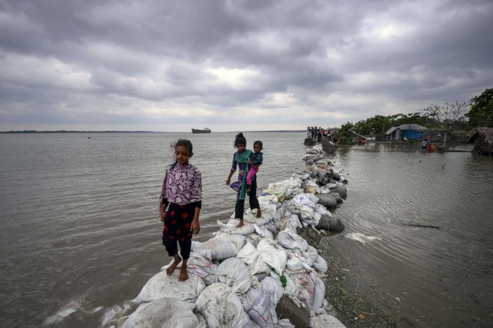 Bangladeshi children walk over the top of a sandbag embankment that was breached by high waters in Khulna on May 4, 2019, as Cyclone Fani reached Bangladesh. - Cyclone Fani, one of the biggest to hit India in years, barrelled into Bangladesh on May 4 afte
