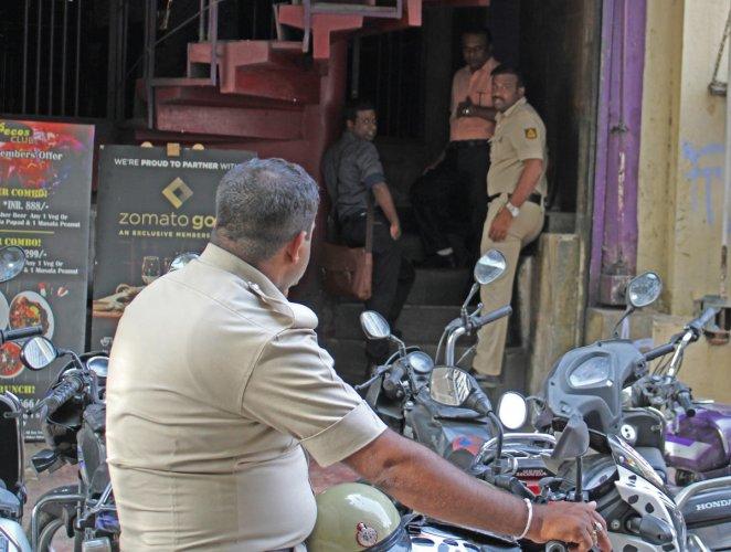 Policemen inspect CCTV cameras at a bar on Brigade Road in Bengaluru on Saturday. DH Photo/Madan K