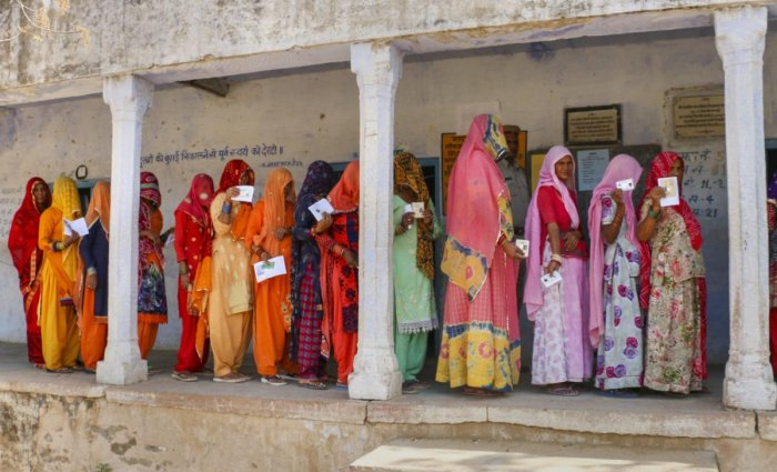 Voters show their ID cards as they wait in a queue at a polling station, during the fifth phase of Lok Sabha elections, in Nagaur district. PTI photo