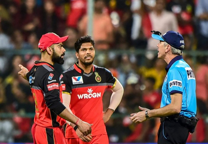 RCB captain Virat Kohli has a word with umpire Nigel Llong after he wrongly adjudged a Umesh Yadav delivery as no-ball. PTI