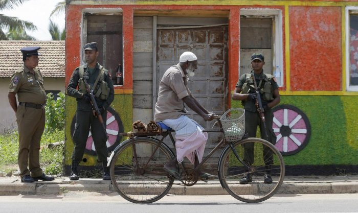 A Sri Lankan Muslim rides past soldiers securing a Muslim neighborhood following overnight clashes in Poruthota, a village in Negombo, about 35 kilometers North of Colombo, Sri Lanka, Monday, May 6, 2019. AP/PTI