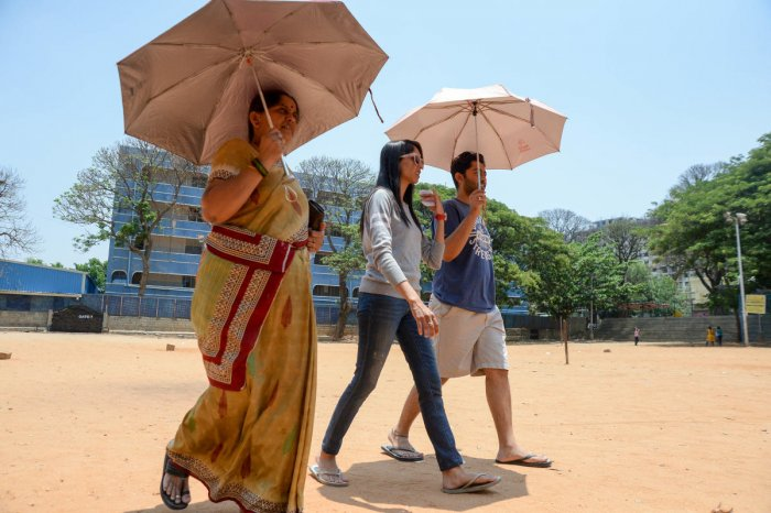 People carry umbrellas to take protection from the heat at a polling booth in Padmanabhanagar. DH photo/Satish Badiger