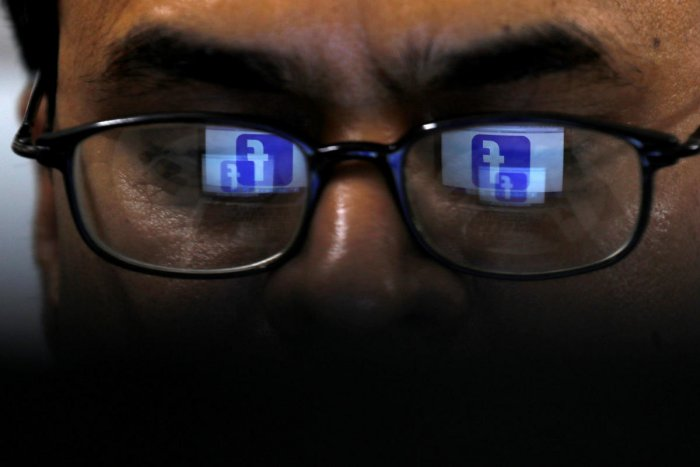 FILE PHOTO: Facebook logo is reflected in glasses in this picture illustration taken April 1, 2019. REUTERS/Akhtar Soomro/Illustration/File Photo