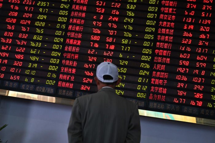 Investors monitor stock price movements at a securities company in Shanghai on May 8, 2019. - A red wave swept across Asia trading floors, as investors grow increasingly concerned that the China-US trade deal, which appeared all by ready to sign, could fa