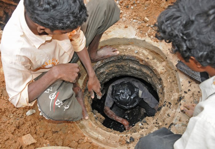 Workers clean a manhole without gloves and shoes at Siddegowda Street, near KH (Double) Road, Bengaluru. This picture was taken in 2013, after the High Court had instructed BWSSB to procure cleaning machines to prevent accidents. DH PHOTO BY S K DINESH