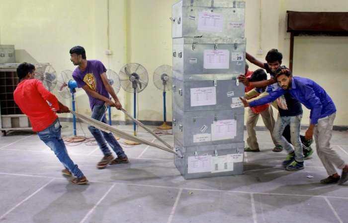 Workers shift election material at a distribution centre for the upcoming Lok Sabha elections in Thane on Wednesday. PTI
