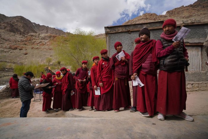 Buddhist monks wait outside a polling station to vote near the Hemis Monastery about 45km from Leh in India's Ladakh region on May 6, 2019. - India held on May 6 the fifth phase of its marathon election, with 90 million people eligible to vote in key seats for Prime Minister Narendra Modi's party and security heavy in restive Kashmir. (AFP)