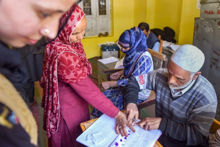 An elderly voter puts her thumb impression before casting her vote at a polling station during the third phase of Lok Sabha elections, in Anantnag on April 23, 2019. PTI