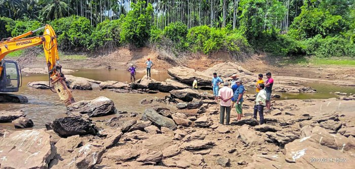 An earth mover pressed to service to remove silt and boulders to facilitate easy flow of water from River Swarna to Baje dam in Udupi.