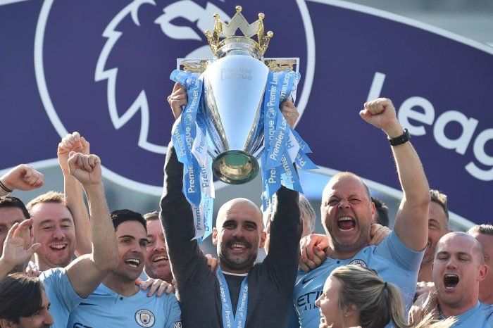 TOPSHOT - Manchester City's Spanish manager Pep Guardiola holds up the Premier League trophy as he's surrounded by his staff after their 4-1 victory in the English Premier League football match between Brighton and Hove Albion and Manchester City at the A
