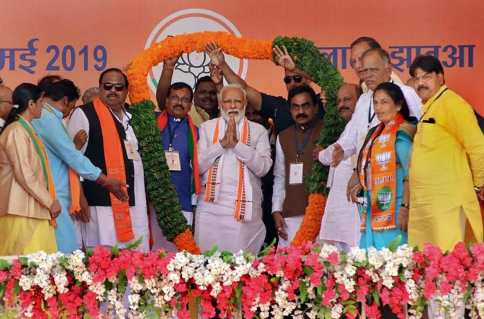 Prime Minister Narendra Modi being garlanded during an election campaign rally for the ongoing Lok Sabha polls, in Ratlam, on May 13, 2019. PTI