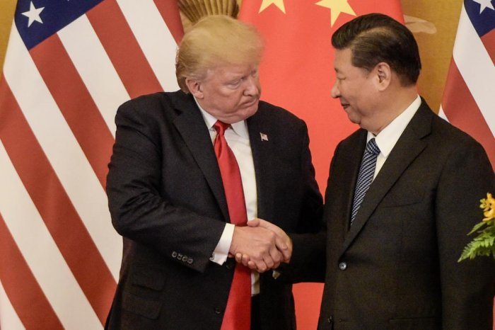 (FILES) In this file photo taken on November 09, 2017, US President Donald Trump (L) shakes hand with China's President Xi Jinping at the end of a press conference at the Great Hall of the People in Beijing. - China said Monday, May 13, 2019 it will raise