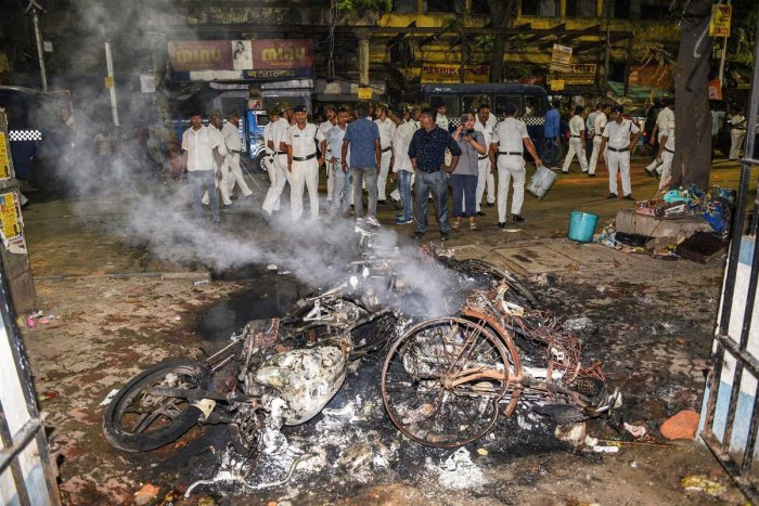 Police personnel look on near vehicles burnt by a mob during BJP President Amit Shah's election roadshow for the last phase of Lok Sabha polls, in Kolkata, Tuesday, May 14, 2019. (PTI Photo)