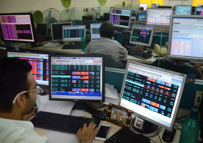 Sharebrokers and holders check the Sensex and Nifty at a Share market. Domestic equities took a beating amid a global selloff after US President Donald Trump imposed USD 60 billion tariffs on Chinese imports, a move that has fuelled concerns of an interna