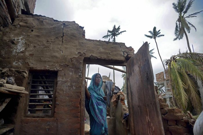 Puri: A woman stands in the remnants of her home in the aftermath of the cyclone 'Fani', at the heritage crafts village Raghurajpur, in Puri district. (PTI File Photo)