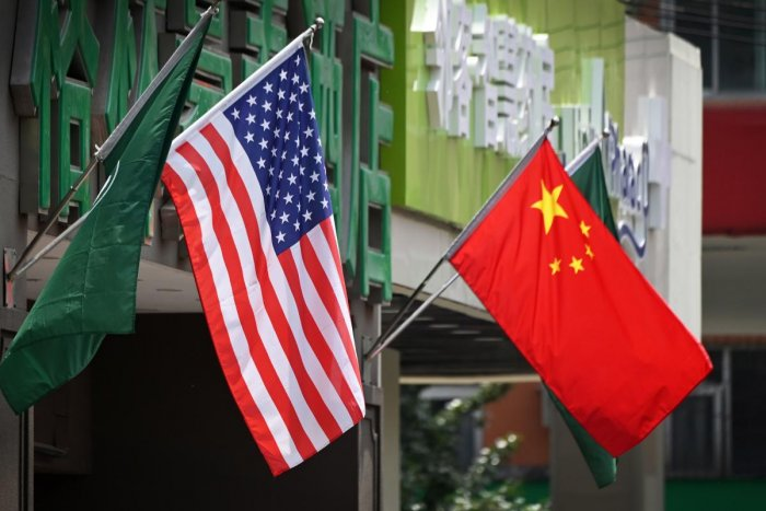 The US (L) and Chinese flags are displayed outside a hotel in Beijing on May 14, 2019. - Beijing's latest retaliation against US tariff hikes -- an increase on $60 billion of US imports from June 1 -- could leave China running low on ammunition in the tra
