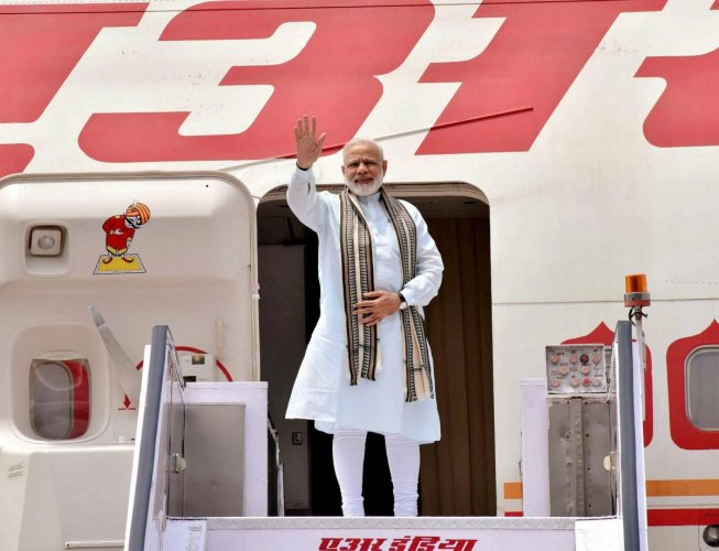 New Delhi: Prime Minister Narendra Modi waves before his departure from New Delhi. (PTI Photo)
