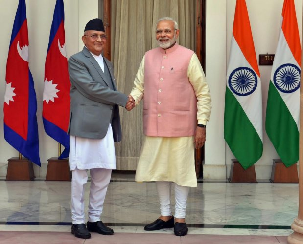 Prime Minister Narendra Modi shakes hands with his Nepalese counterpart Khadga Prasad Oli before their meeting at Hyderabad House in New Delhi on Saturday. (PTI Photo)