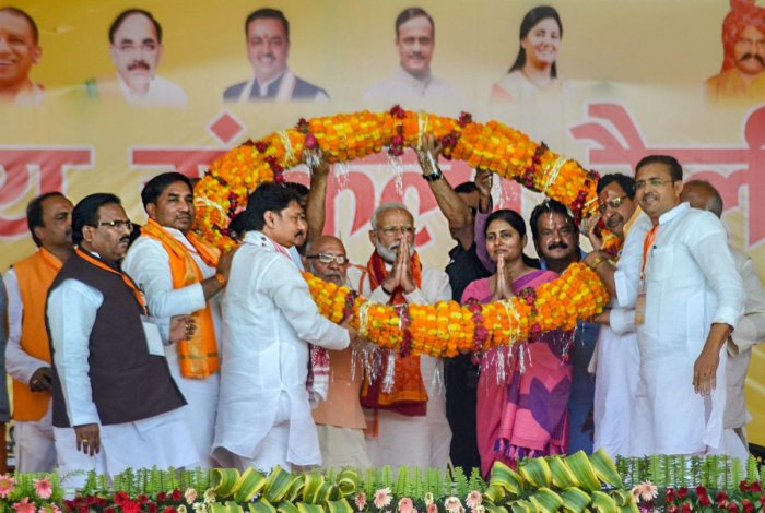 Prime Minister Narendra Modi with NDA candidate for Mirzapur parliamentary seat Anupriya Patel (R) being garlanded during an election campaign rally for the ongoing Lok Sabha polls, in Mirzapur, Thursday, May 16, 2019. (PTI Photo)