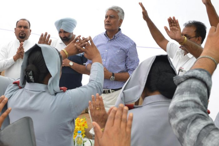 Indian National Congress party Punjab president and candidate for Gurdaspur Sunil Kumar Jakhar (C) along with Christians priests offer prayers as he campaigns ahead of the Lok Sabha election at the Salvation Army Central Corps. (Photo by AFP)
