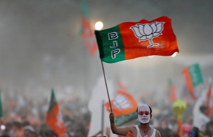 A supporter of India's ruling Bharatiya Janata Party (BJP) waves the party flag during an election campaign rally being addressed by India's Prime Minister Narendra Modi (Photo Modi).