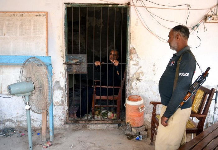 In this image taken on May 9, 2019, a Pakistani local pediatrician alleged to have been responsible for the HIV outbreak, Dr. Muzaffar Ghangro, is seen behind the bars as a police personnel looks on at a local police station in Rato Dero in the district of Larkana of the southern Sindh province. (AFP Photo)