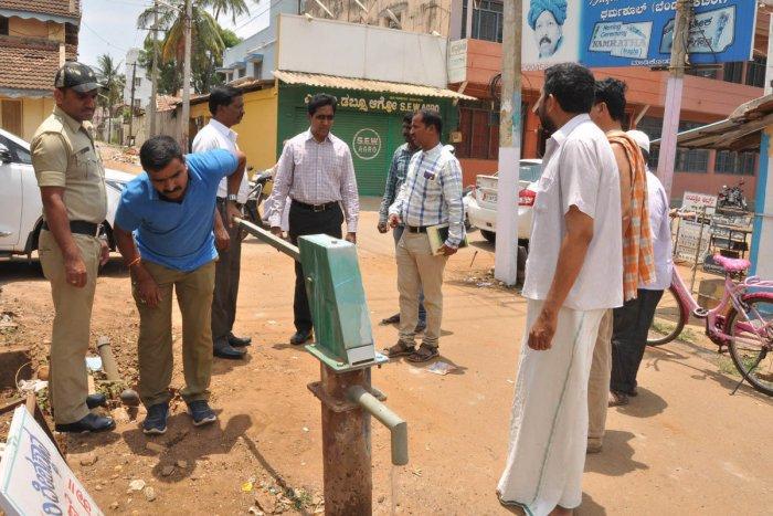 Chikkamagaluru Deputy Commissioner Dr Bagadi Gautam inspects a borewell in Gowrikaluve on Thursday. City Municipal Council K Parameshwar is present.