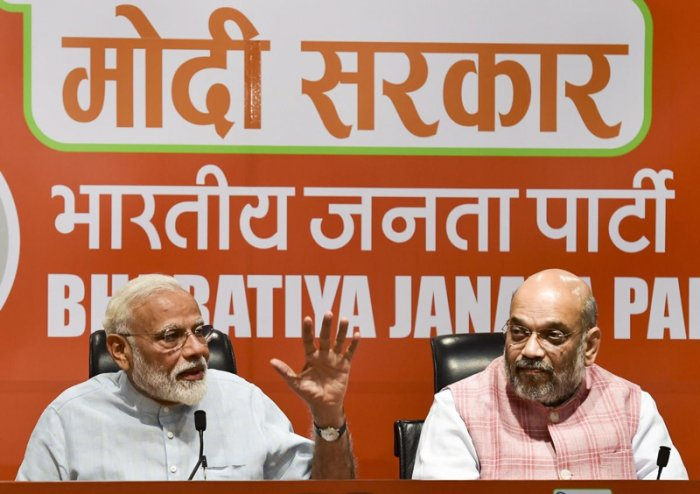 Prime Minister Narendra Modi speaks as BJP President Amit Shah looks on during a press conference at the party headquarters in New Delhi. (PTI Photo)