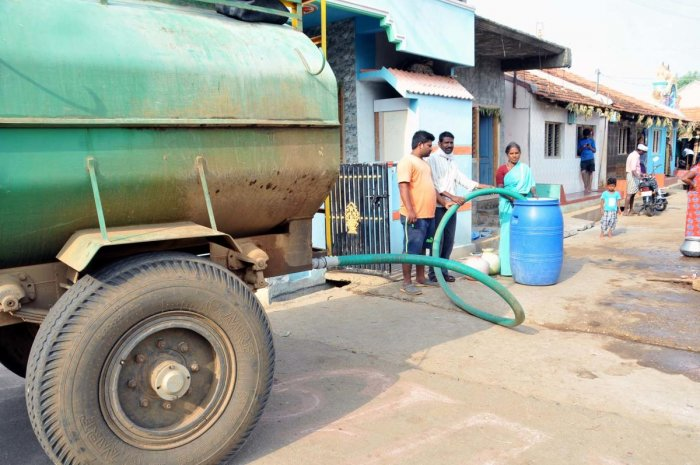 Residents of Hiregowja collect water from tanks.