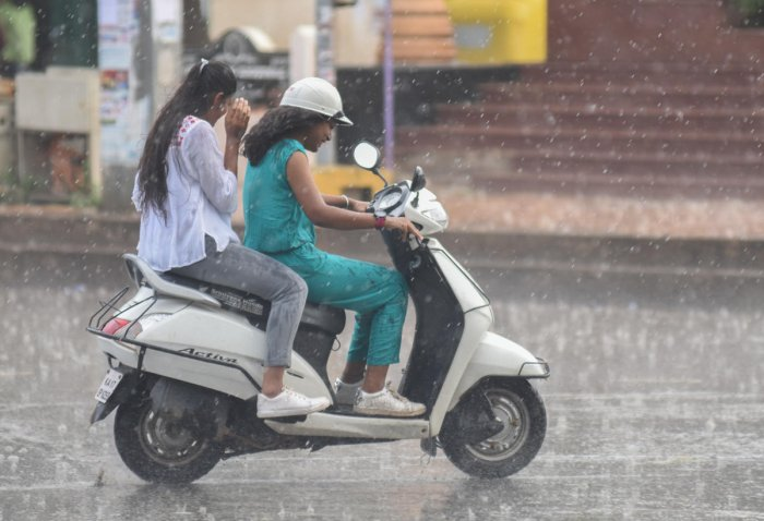 Sudden rain in city, people seen protecting themselves with umbrella, vehicle riders move in rain. File photo