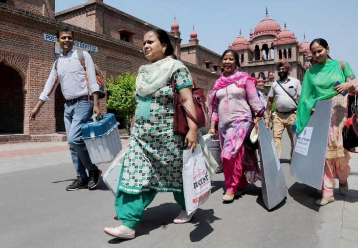 Election officials carry EVM and VVPAT machines and other equipments ahead of the seventh and last phase of Lok Sabha polls. (Photo PTI)