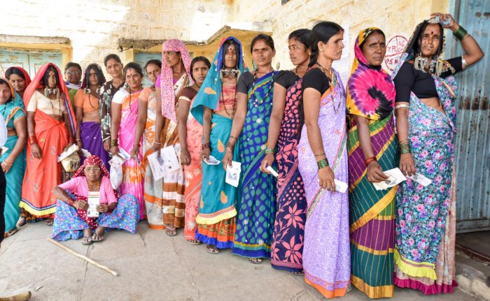 Women wait in a queue to exercise their franchise in the bypoll, at a polling booth at Koravi Dodda tanda in Chincholi Assembly constituency, Kalaburagi district, on Sunday. DH Photo/Prashanth H G