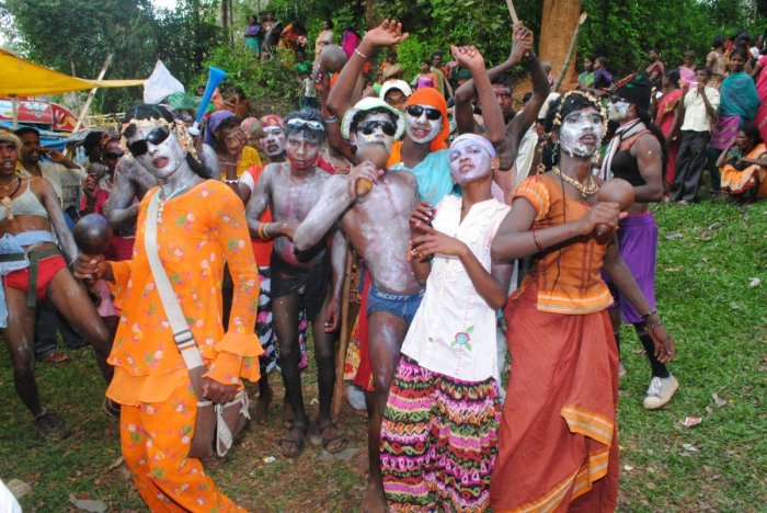 Men wearing weird makeup and costumes dance on the occasion of 'Kunde Habba'.