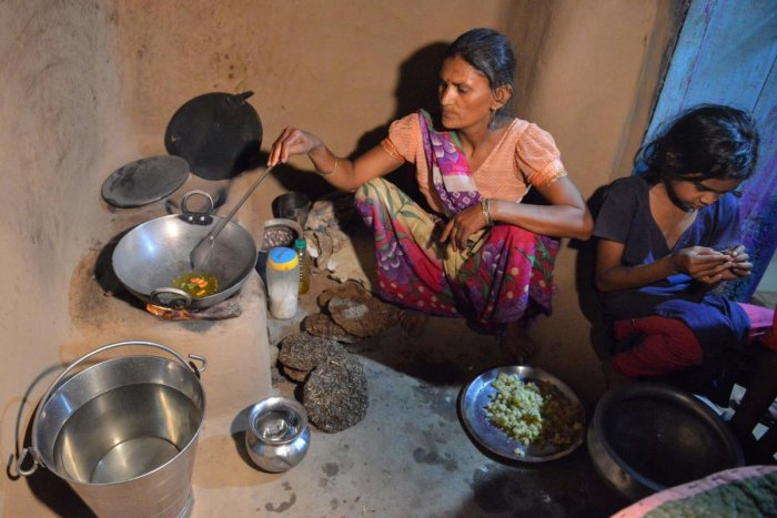 """In this photograph taken on April 8, 2019, Indian woman Jamintra Devi (C) prepares food on a traditional earthen stove in Nisarpura village on the outskirts of Patna. - Reena Devi says her life changed when she got a cooking gas connection under a programme championed by India's Prime Minister Narendra Modi. But the """"free"""" kit came at a price. (Photo AFP)"""
