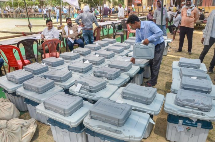 A man arranges Electronic Voting Machines(EVM),and VVPATs at a distribution centre on the eve of the seventh and last phase of Lok Sabha polls in Mirzapur. PTI photo