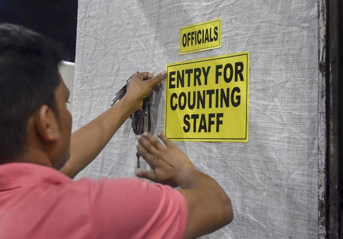 A worker pastes notice on a wall outside a counting centre ahead of the 2019 Lok Sabha elections results, at Netaji Indoor Stadium in Kolkata. PTI photo