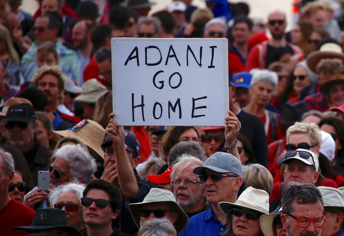 A protester holds a sign as he participates in a national Day of Action against the Indian mining company Adani's planned coal mine project in north-east Australia, at Sydney's Bondi Beach in Australia. (Reuters File Photo)