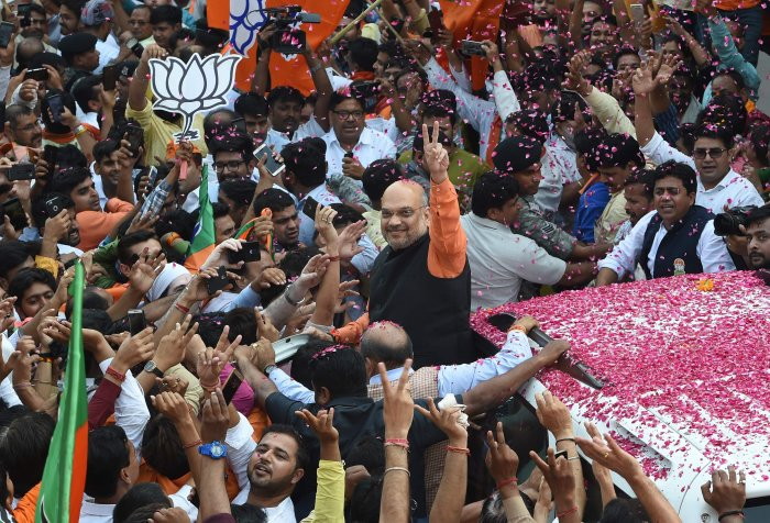 """Amit Shah (C), president of the ruling Bharatiya Janata Party (BJP), gestures to supporters during victory celebrations in the Indian national elections in New Delhi on May 23, 2019. - India's Prime Minister Narendra Modi claimed victory May 23 in the country's elections, promising an """"inclusive"""" future after his Hindu nationalist party appeared headed for a landslide win. (Photo by AFP)"""