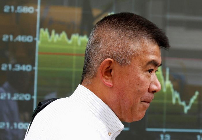 A passerby stands in front of an electronic board displaying a graph showing recent movement of Japan's Nikkei average outside a brokerage in Tokyo. Reuters